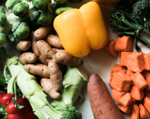 a bunch of seasonal autumn veggies like brussels sprouts, sweet potato, bell peppers, and broccoli